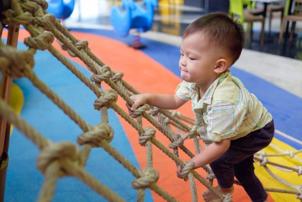 a child climbing a wooden ladder connecting to a playground