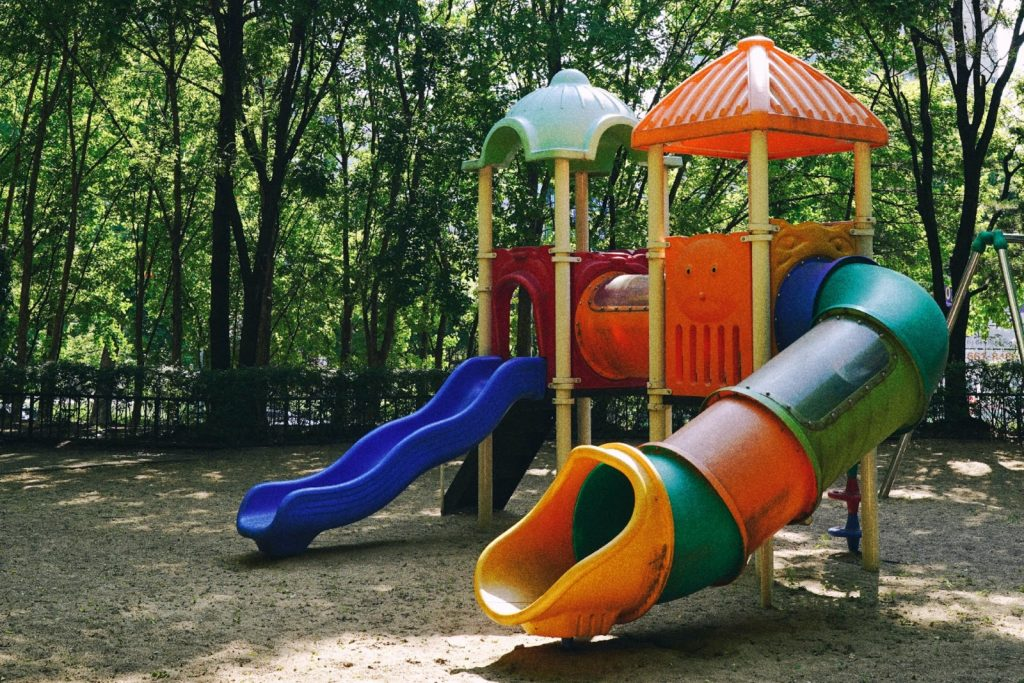 a playground with a tube slide and an open slide