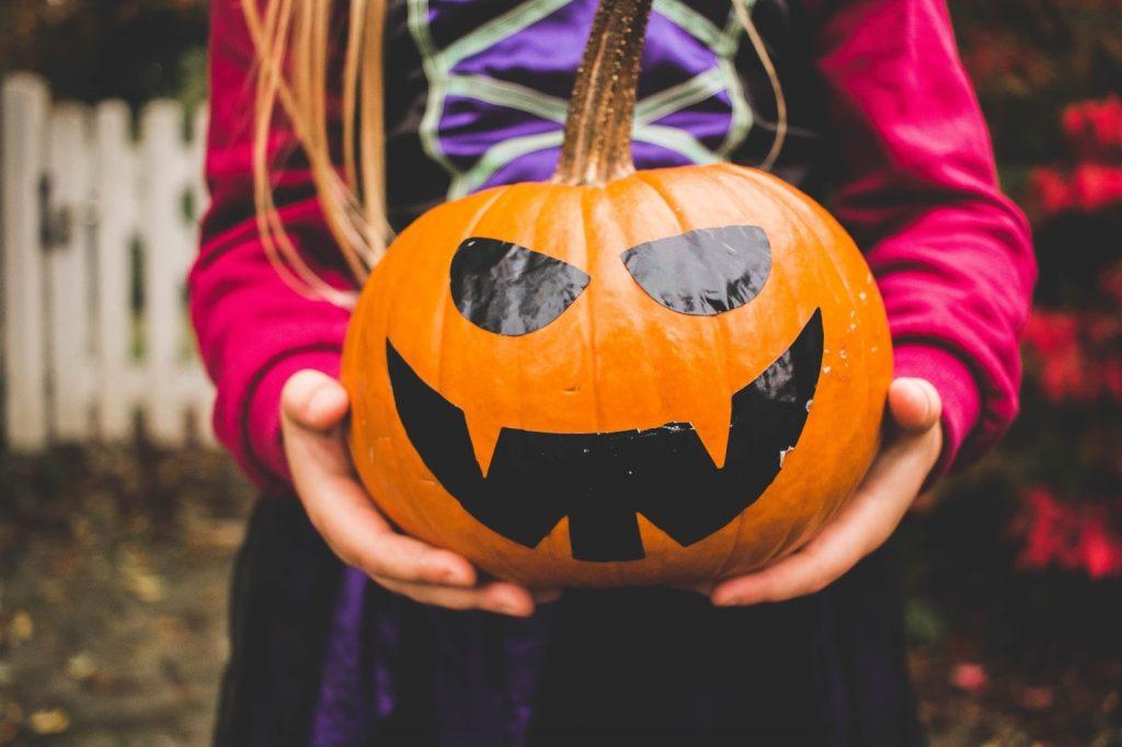 a young girl holding a pumpkin