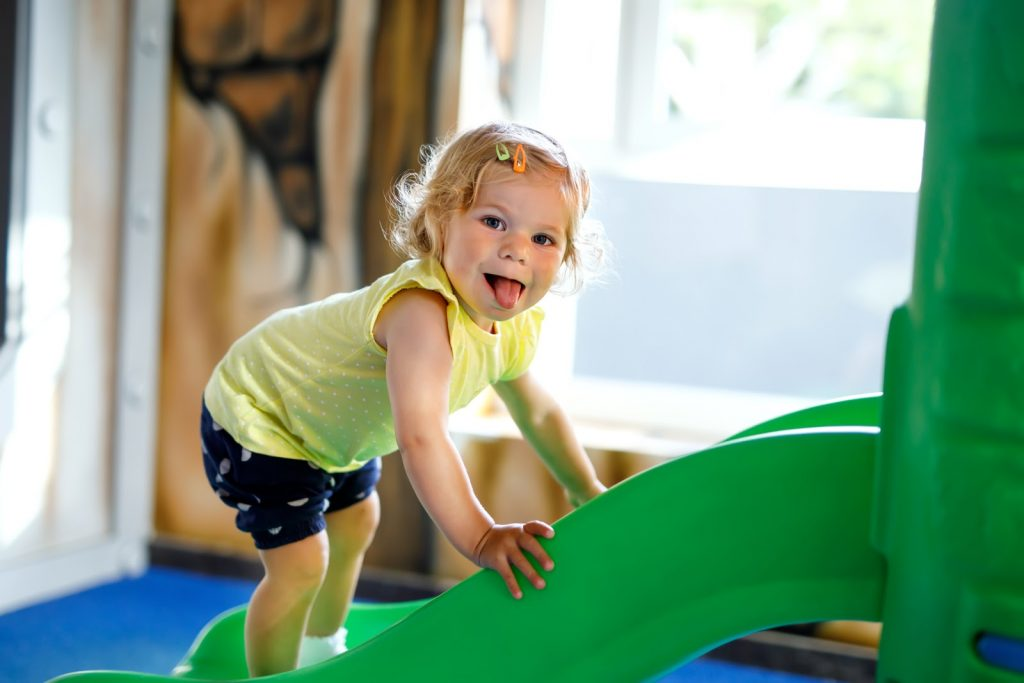 a toddler playing on a slide and sticking her tongue out