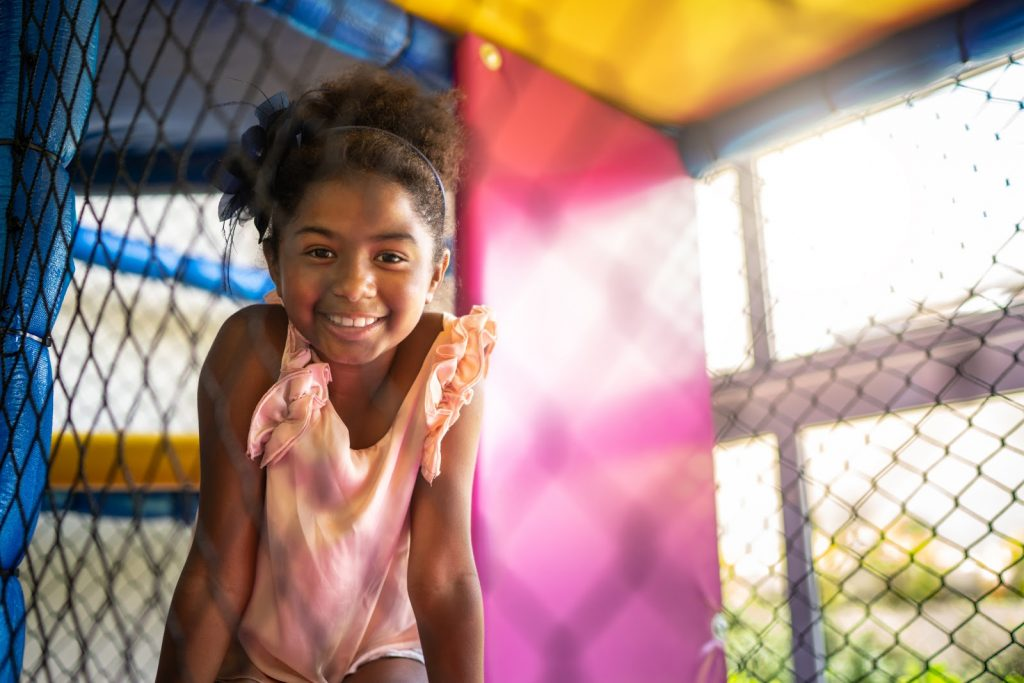 a young girl inside a play space smiling